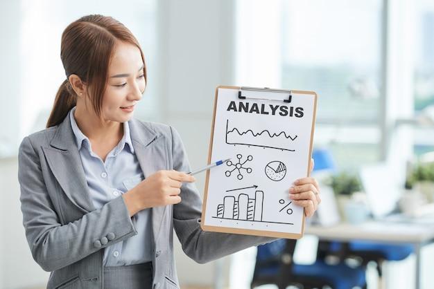 Femme asiatique en costume debout dans le bureau et pointant sur le presse-papiers avec affiche et mot Photo gratuit