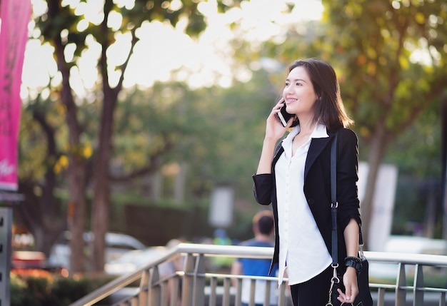 Femme asiatique debout en plein air. bonne femme parlant au téléphone. Photo Premium