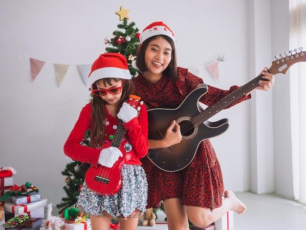Une femme asiatique et un enfant célèbrent noël en gratifiant la guitare dans la maison. une fille joue une chanson avec un sourire le jour de noël. Photo Premium