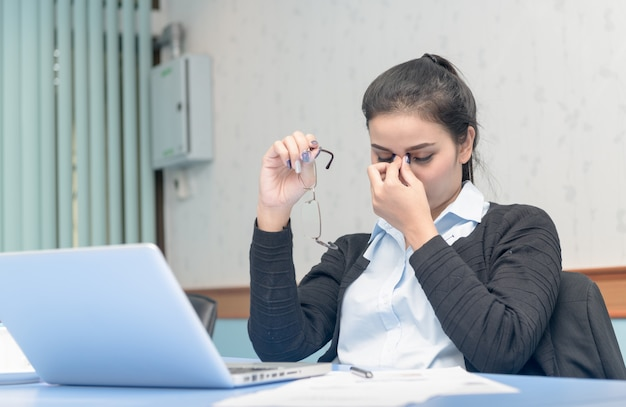 Femme asiatique a eu mal à la tête de travailler sur un ordinateur portable toute la journée, computer vision syndrome Photo Premium