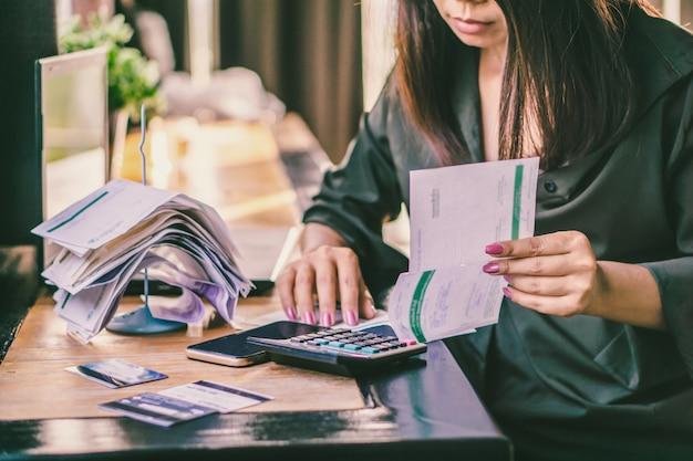 Femme asiatique avec des factures financières, calcul de la dette Photo Premium