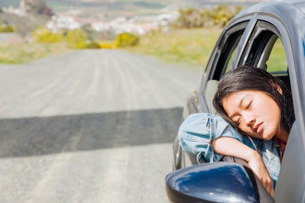 Femme asiatique, faire la sieste, dans voiture, pendant, roadtrip Photo gratuit