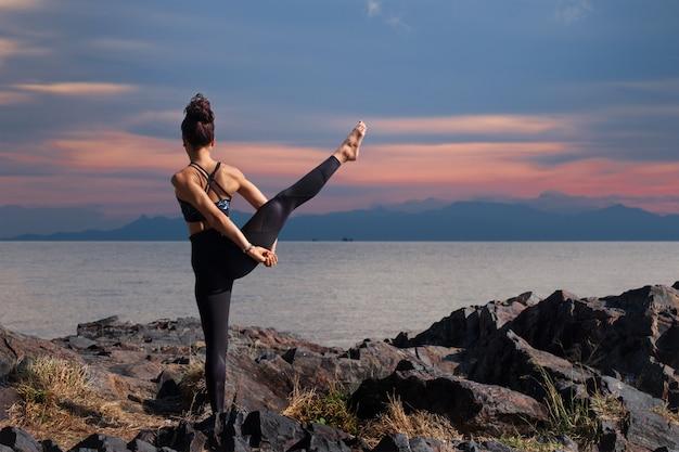 Femme asiatique faisant une pose de yoga pour l'équilibre et l'étirement. Photo Premium