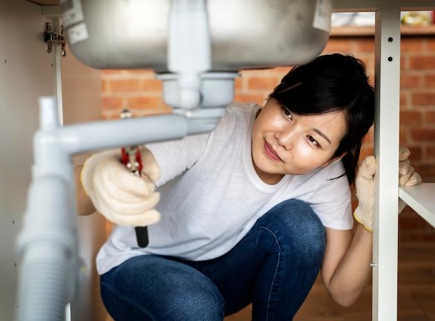 Femme asiatique, fixation, évier cuisine Photo Premium
