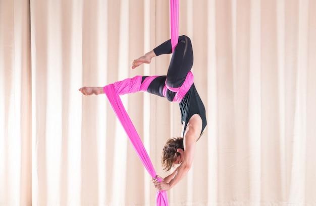 Femme asiatique de formation dans la salle de fitness avec des éléments de yoga mouche Photo Premium