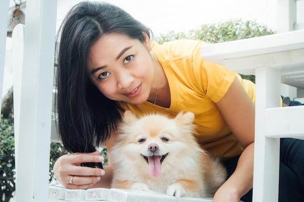 Femme asiatique joue avec son chien poméranien. Photo Premium