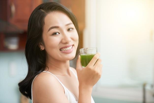 Femme asiatique joyeuse avec un verre de jus vert Photo gratuit
