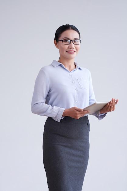 Femme asiatique à lunettes, chemisier élégant et jupe qui pose en studio avec tablette Photo gratuit