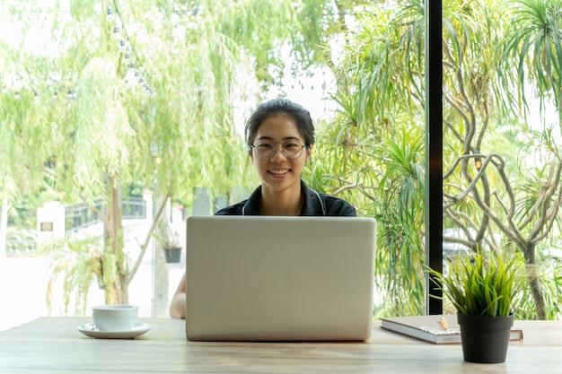 Femme asiatique avec des lunettes souriant à l'aide d'ordinateur portable avec une tasse de café sur la table. Photo Premium