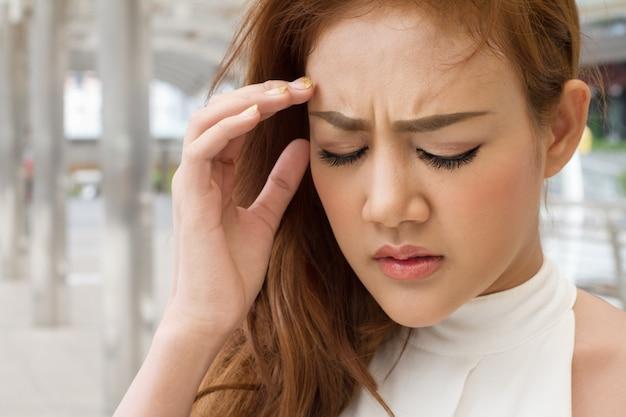 Femme asiatique malade souffre de maux de tête, migraine, vertiges, vertiges Photo Premium