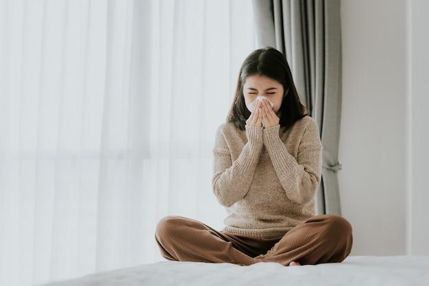 Femme asiatique malade utilisant un mouchoir pour éternuer à la maison Photo Premium