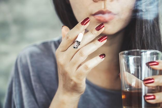 Femme asiatique malsaine fumer et boire de l'alcool Photo Premium