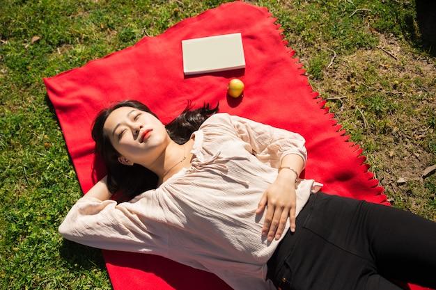 Femme asiatique, mensonge, dormir, sur, pelouse Photo gratuit