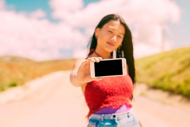 Femme asiatique montrant un smartphone avec écran blanc Photo gratuit