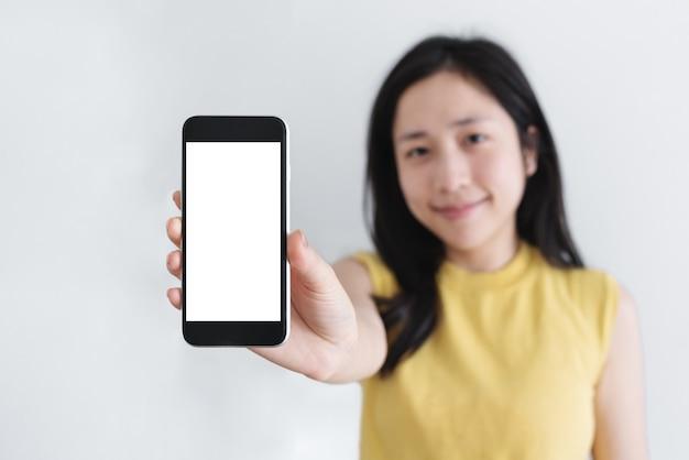 Femme Asiatique Montrant Un Téléphone Intelligent Mobile Avec Un Visage Souriant, Un écran Blanc Vide Photo Premium