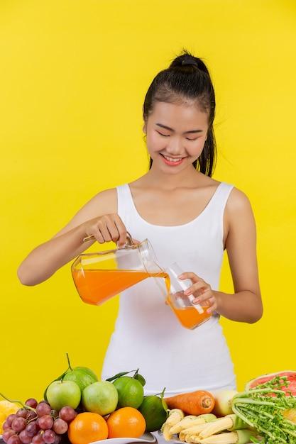 Une femme asiatique portant un débardeur blanc. verser le jus d'orange dans un verre et sur la table il y a beaucoup de fruits. Photo gratuit