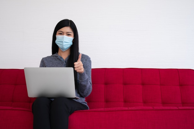 Femme Asiatique Portant Un Masque Facial Et Utilisant Un Ordinateur Portable Sur Le Canapé Pour Travailler à Domicile Et Les Pouces Vers Le Haut. Photo Premium