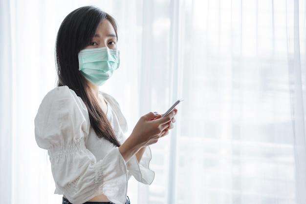 Femme Asiatique Portant Un Masque Protecteur Et à L'aide De Smartphone Mobile Photo Premium