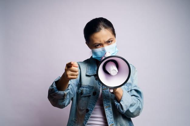 Femme Asiatique Portant Un Masque Protecteur Criant Avec Mégaphone Isolé. Photo Premium