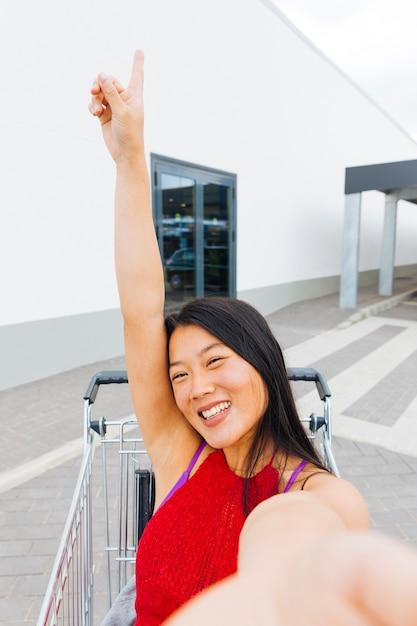 Femme asiatique, poser, prendre, selfie, dans, chariot Photo gratuit