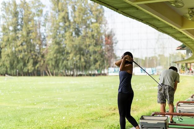 Femme asiatique pratiquant son swing au practice de golf. Photo Premium