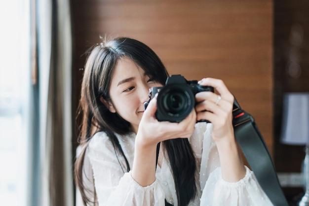 Femme Asiatique Prenant La Photo Par Appareil Photo Numérique Sans Miroir, Avec Visage Souriant Photo Premium