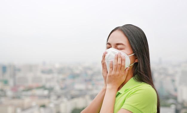 Femme asiatique qui respire en portant un masque de protection contre la pollution de l'air dans la ville de bangkok. Photo Premium