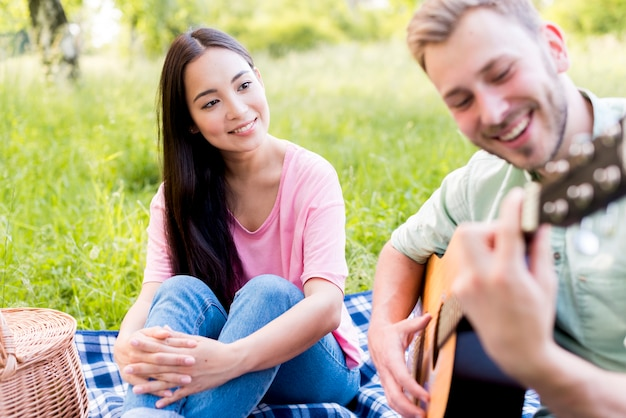 Femme Asiatique, Regarder, Jouer, Guitare Photo gratuit