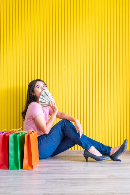 Femme Asiatique Avec Des Sacs Couvrant Sa Bouche Avec Des Notes Photo Premium