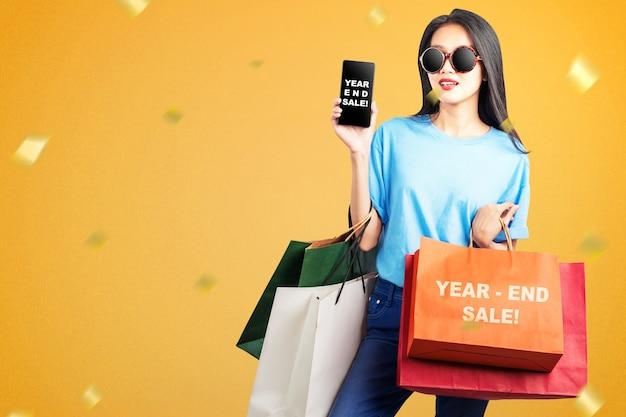 Femme Asiatique Avec Des Sacs à Provisions Montrant L'écran Du Téléphone Mobile Avec Texte De Vente De Fin D'année. Bonne Année 2021 Photo Premium
