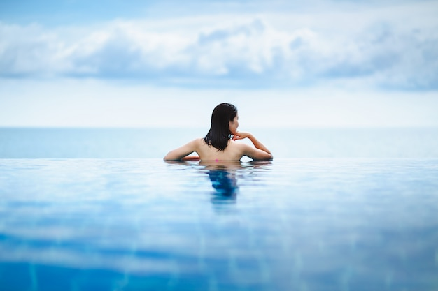 Femme asiatique se détendre dans la piscine sur la plage Photo Premium