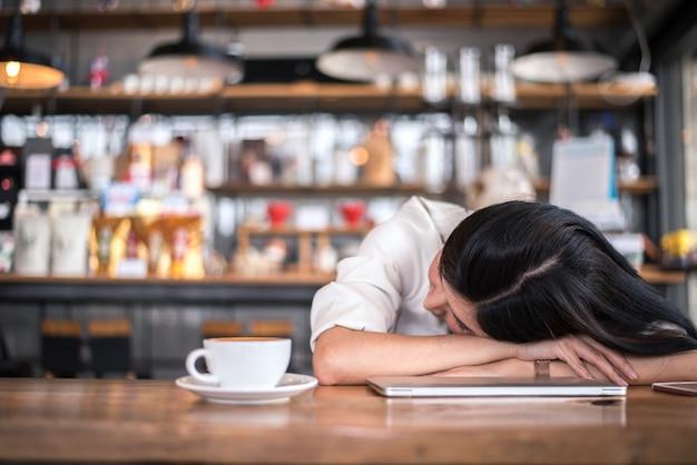 Femme asiatique se repose et dort dans un café parce qu'elle est fatiguée de travailler Photo Premium