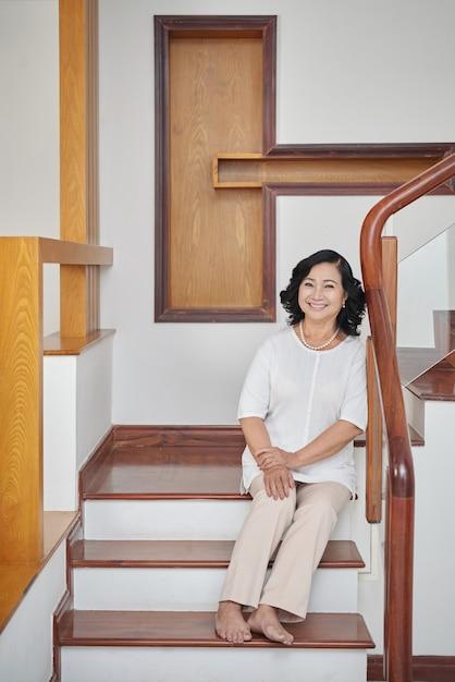 Femme asiatique senior gaie assis dans les escaliers à la maison Photo gratuit