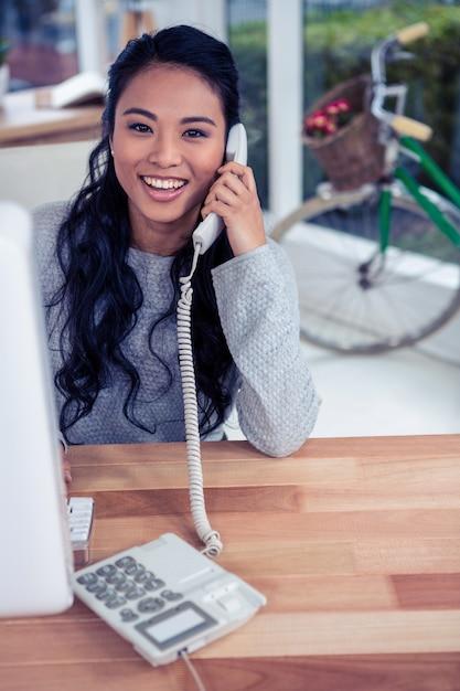 Femme asiatique souriante sur appel téléphonique en regardant la caméra au bureau Photo Premium