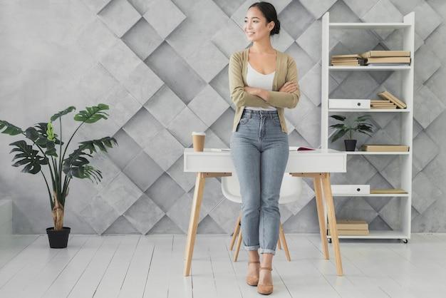 Femme asiatique souriante dans son bureau Photo gratuit