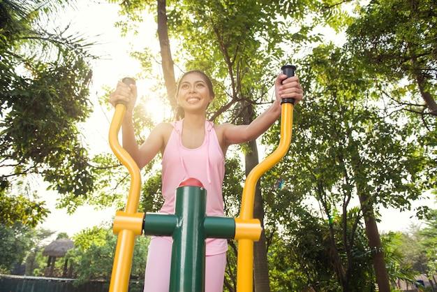 Femme asiatique souriante fait une séance d'entraînement sur une machine elliptique Photo Premium