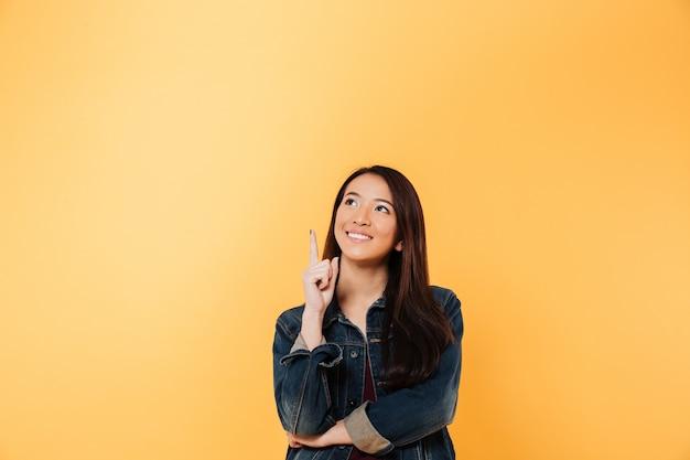 Femme Asiatique Souriante En Veste En Jean Pointant Et Levant Sur Fond Jaune Photo gratuit