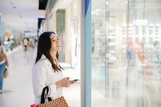 Femme asiatique sourire avec des sacs à provisions profiter dans un centre commercial Photo Premium
