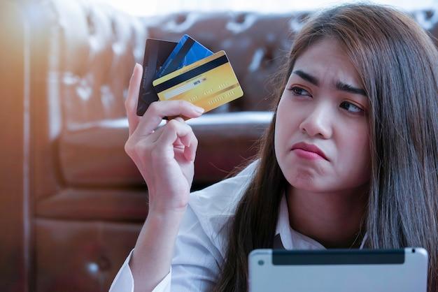 Femme asiatique stressée, confuse, regardant trop de cartes de crédit en main. Photo Premium