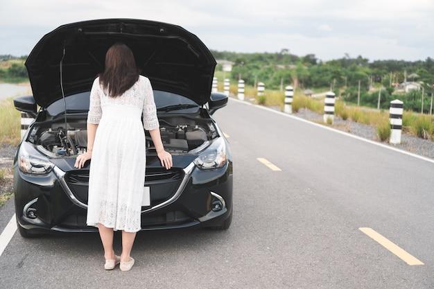 Femme asiatique stressée ouvrant le capot, à la recherche d'une voiture cassée et vérifiant le moteur sur une route de campagne. Photo Premium