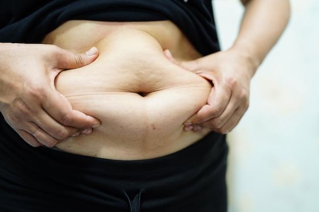 Femme asiatique en surpoids montre le gros ventre au bureau. Photo Premium