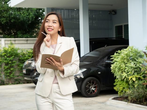 Femme asiatique tenant le cahier en se tenant devant la maison. Photo Premium