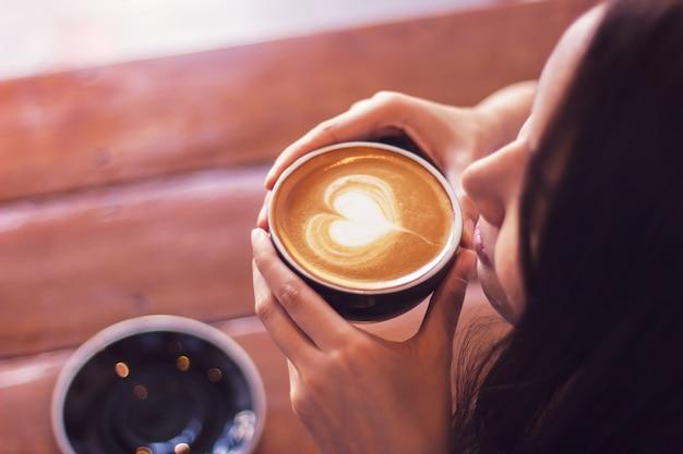Femme asiatique tenant les mains sur une tasse de café. activité de relaxation. boisson préférée. Photo Premium