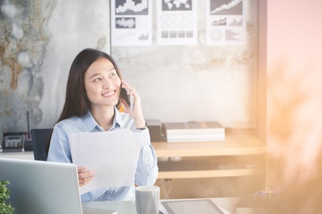 Femme Asiatique Travaillent Heureusement Au Bureau Photo Premium