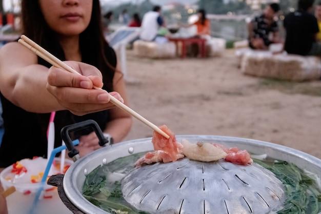 Femme Asiatique Utilisant Des Baguettes Pour Rôtir De La Viande, Des Légumes Et Du Bouillon Thaï Est Appelé Poêle De Porc - Moo Kra Ta. Photo Premium