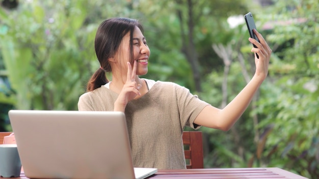 Femme asiatique utilisant un téléphone portable post selfie dans les médias sociaux, femme relax se sentir heureux montrant des sacs à provisions assis sur une table dans le jardin le matin. Photo gratuit