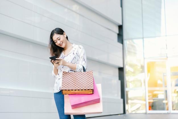 Femme asiatique vérifiant téléphone intelligent et sourire avec des sacs à provisions profiter dans le centre commercial Photo Premium