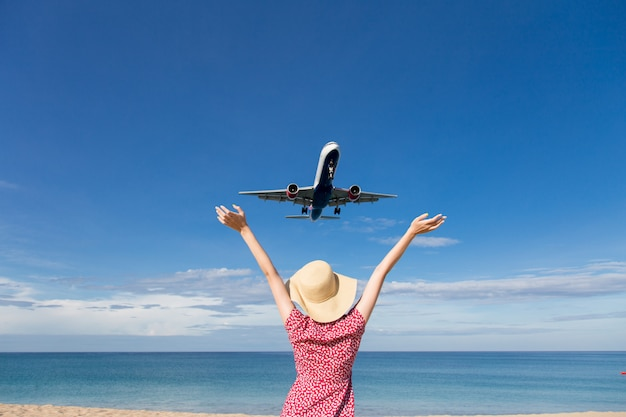 Femme asiatique voyageant se détendre vacances en regardant l'avion volant au-dessus de la mer Photo Premium