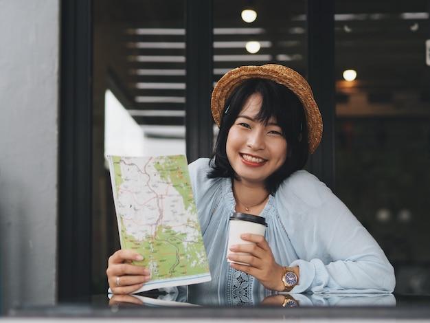 Femme asiatique voyageur se détendre dans un café. Photo Premium