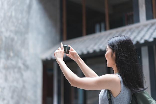 Femme asiatique voyageur utilisant un téléphone portable pour prendre une photo tout en passant un séjour de vacances à pékin, chine Photo gratuit